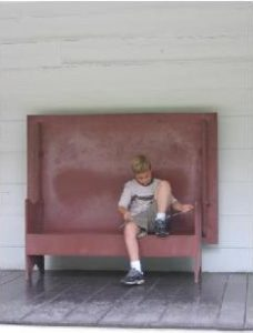 Boy sitting in a big bench, tying his shoe